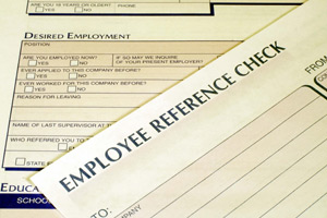 A photograph of a job application and a reference check form. One of the boxes reads: resume fraud.