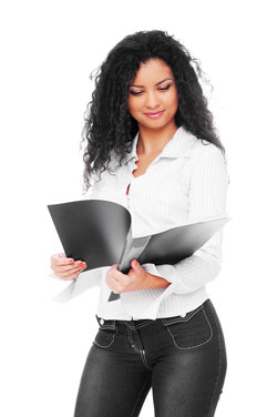 A young woman with long, curly hair is holding a functional resume while standing.